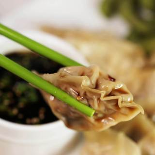 A close up picture of green chopsticks holding a savory potsticker. There's a bowl of dipping sauce in the background and also a plate of Pot stickers to share.