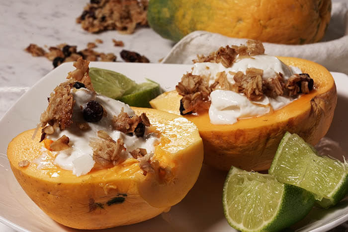 Two halves of papaya filled with creamy yogurt and topped with crunchy granola surrounded by wedges of lime.