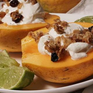 Golden papaya topped with thick greek yogurt, crunchy granola surround by wedges of lime.
