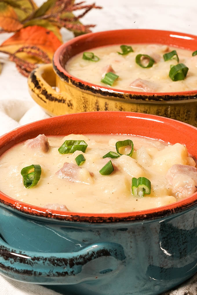 Two bowls filled with Potato Soup with ham.