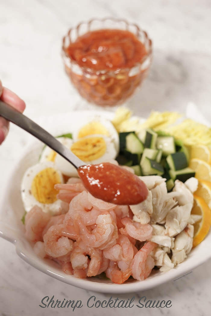 A spoonful of red cocktail sauce over a plate of seafood