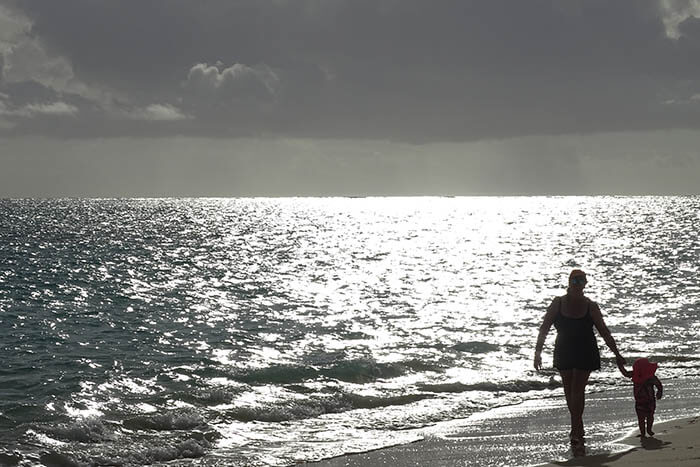 Sunrise on Lanikai Beach. The water sparkles as bright as diamonds with the sky in dark contrast, heavy with clouds. On the beach walks a woman hand in hand with a child.