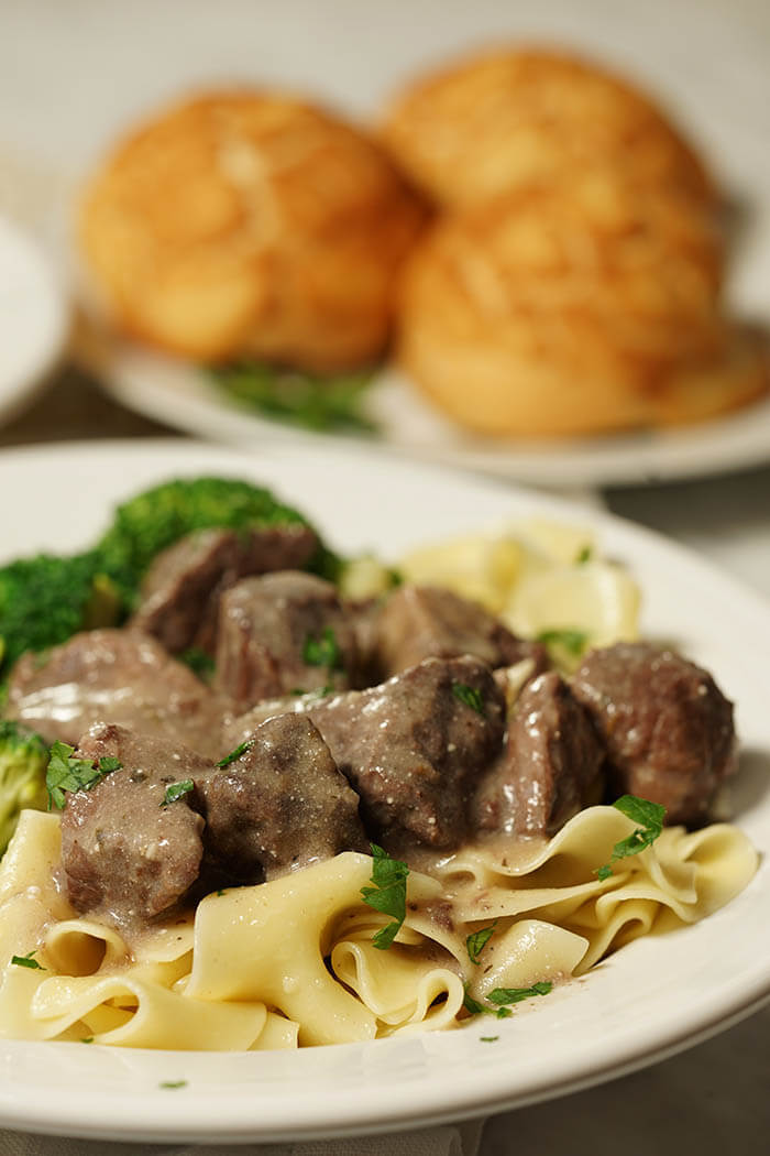 A white bowl full of noodles topped with tender beef tips. Served with a side of broccoli and fresh made rolls. Beef Tips with Gravy Recipe