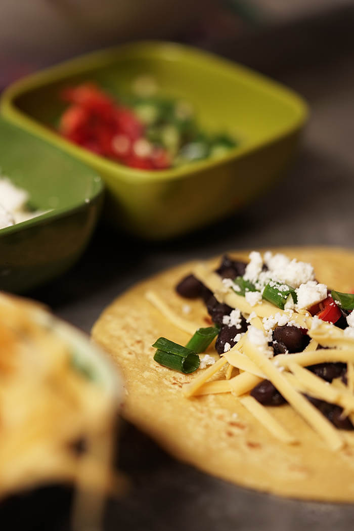 A tortilla piled with black beans, cheddar and Donita cheese and jalapeños.