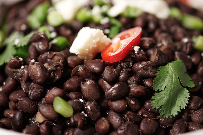A pile of cooked black beans topped with cilantro, cheese and sliced jalapeños peppers.
