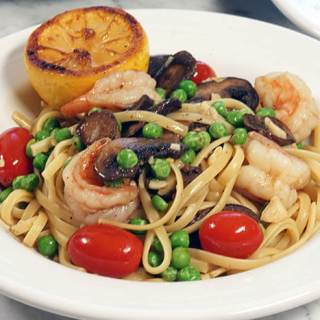 A bowlful of shrimp linguine with a grilled lemon on the side.