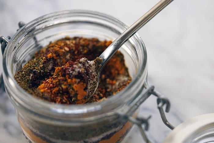A glass jar filled with spice rub.