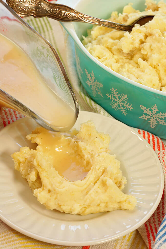 Homemade mashed potatoes on white plate with gravy.