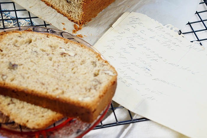 Moist banana nut bread recipe hand written, along with slices of banana bread.