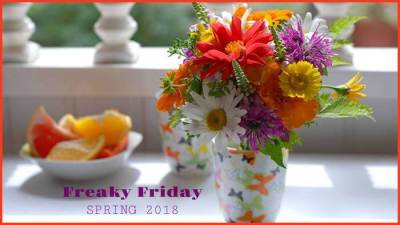 A white countertop with a vase of beautiful spring flower and a bowl of sliced oranges.