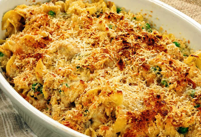 A white casserole dish filled with tuna casserole made with egg noodles. The top has been finished under the broiler and it's golden brown.