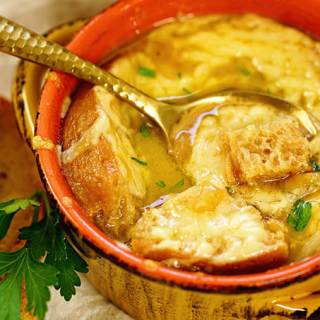 A bowl of homemade french onion soup, with some extra croutons on the side.