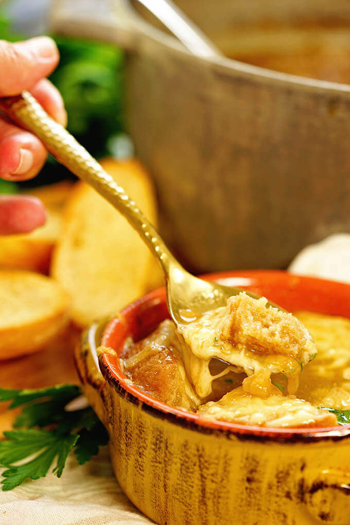 Homemade French Onion Soup in a yellow bowl. A spoon is dipping out a big spoonful!