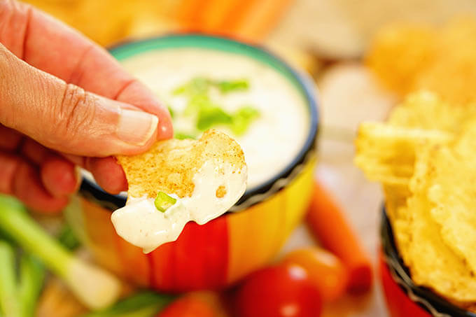 Potato chip dunked into dip.