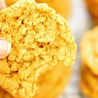Stacks of easy peanut butter oatmeal cookies. One cookie has a bite taken out of it!