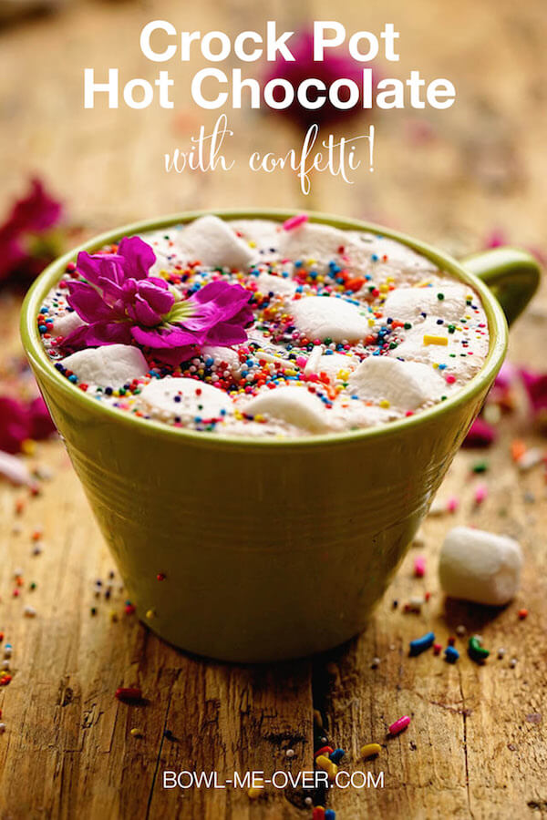 Slow Cooker Hot Chocolate Recipe in a green cup topped with marshmallows and sprinkles