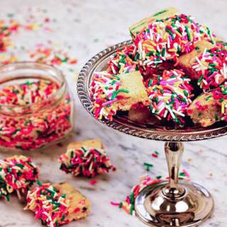 Shortbread cookies on a silver platter on a marble board surround by piles of sprinkles!