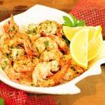 Garlic shrimp in a white bowl with wedges of lemon.