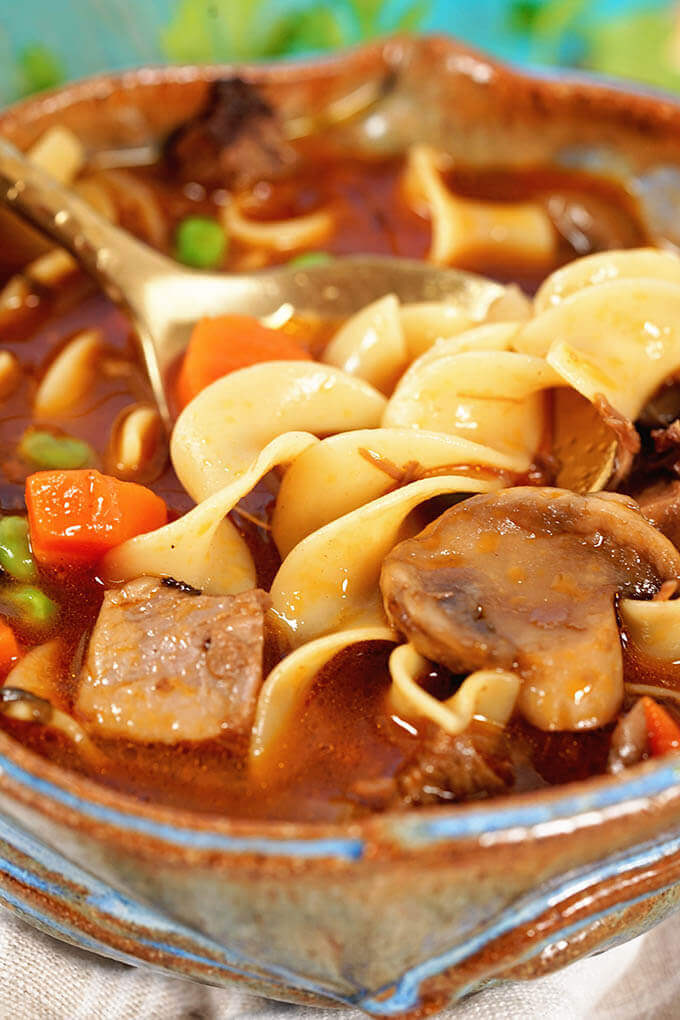 Beef Noodle Soup Recipe with roast beef, noodles, carrots, mushrooms and peas.