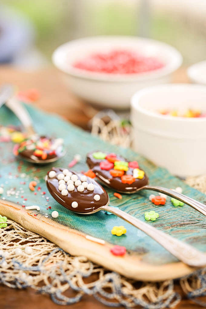 Four Chocolate dipped spoons on blue platter surrounded and topped with sprinkles.