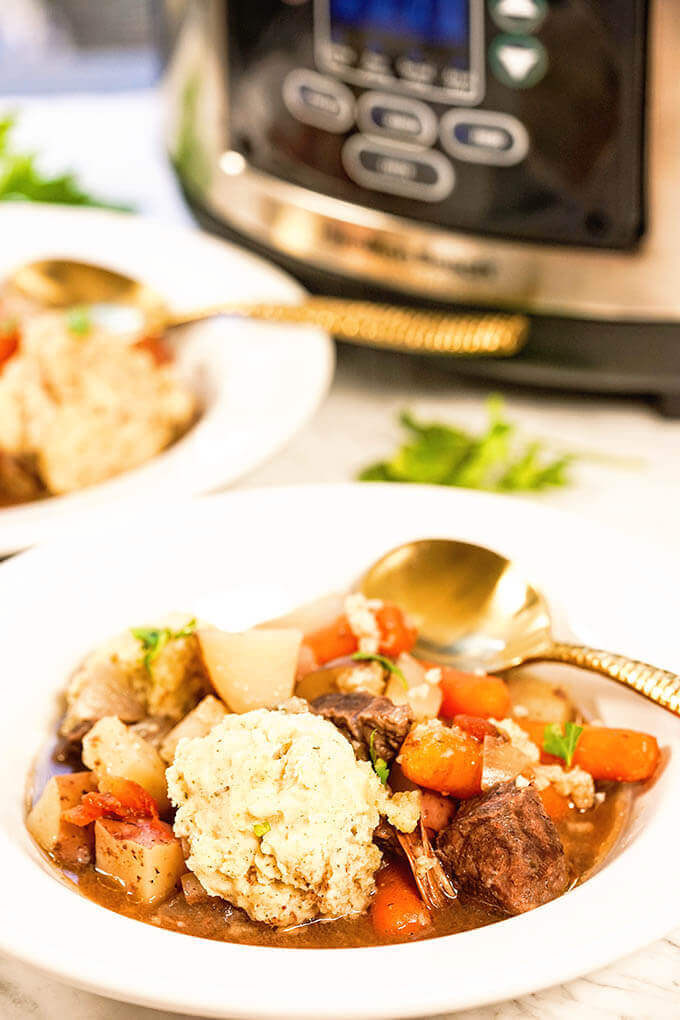 White bowls filled with the BEST Crockpot Beef Stew.