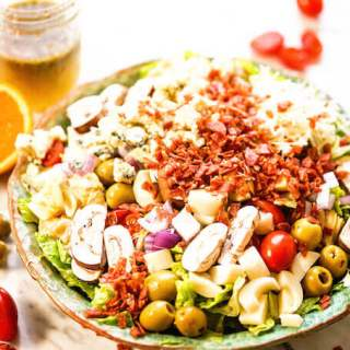 Best green salad in a bowl topped with all the fixings - olives, artichokes, cheese, tomatoes and onions with homemade vinaigrette.