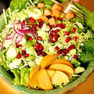 Hand holding green bowl filled with shaved Brussels sprout salad topped with fruit