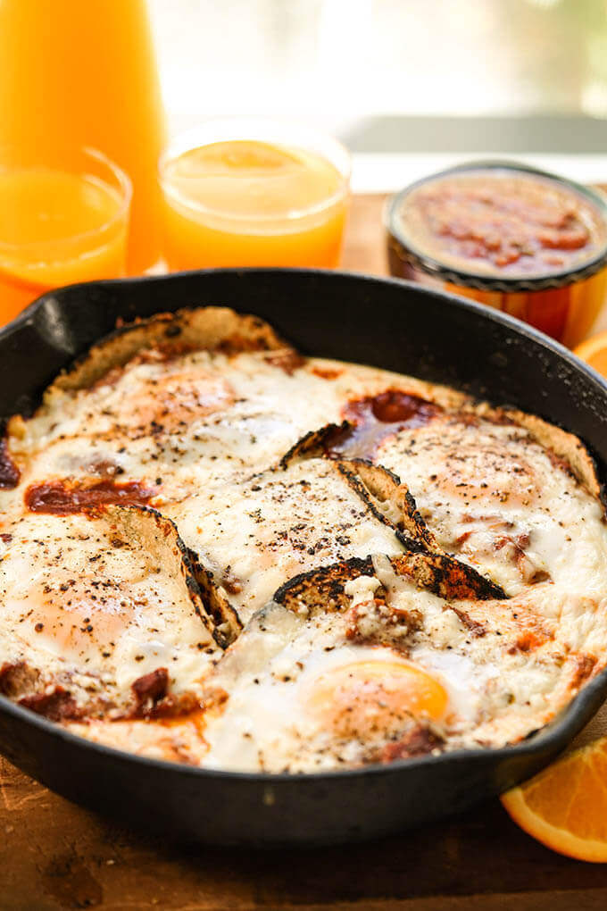 A cast iron skillet filled with Huevos Rancheros recipe serve with fresh squeezed orange juice.