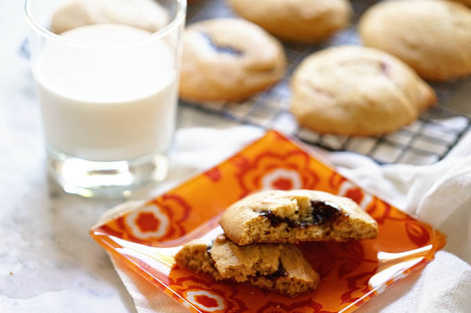 Brown Sugar Cookie filled with fig jam on orange plate with a glass of milk.