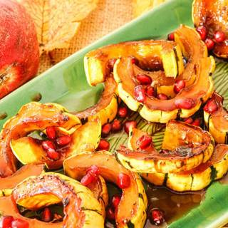 Squash on platter topped with pomegranate seeds
