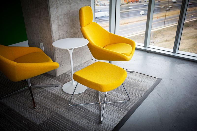 sol en beton cire avec tapis naturel et fauteuils jaunes de designer