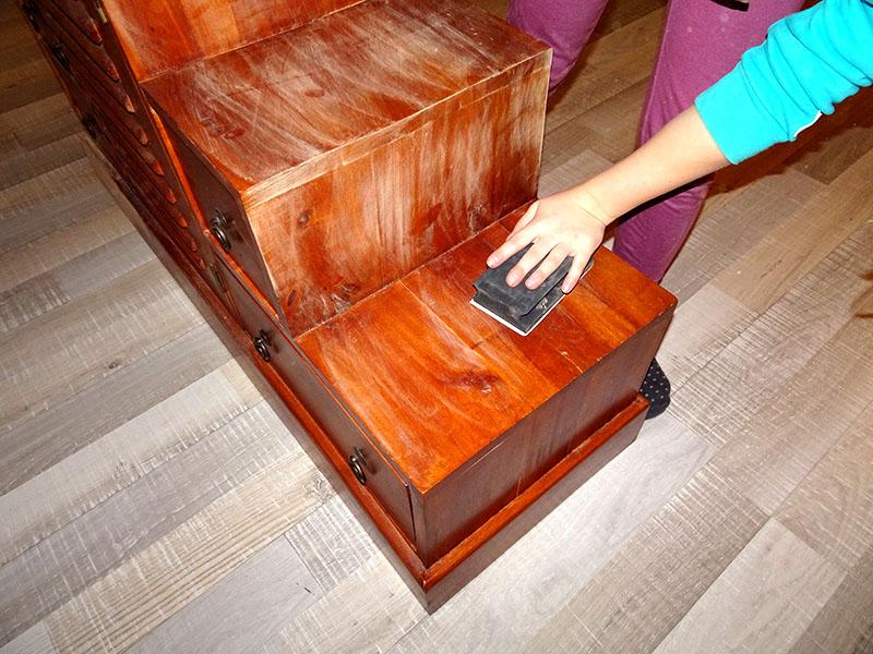 ponçage de la couche de vernis avant de peindre un meuble en couleur