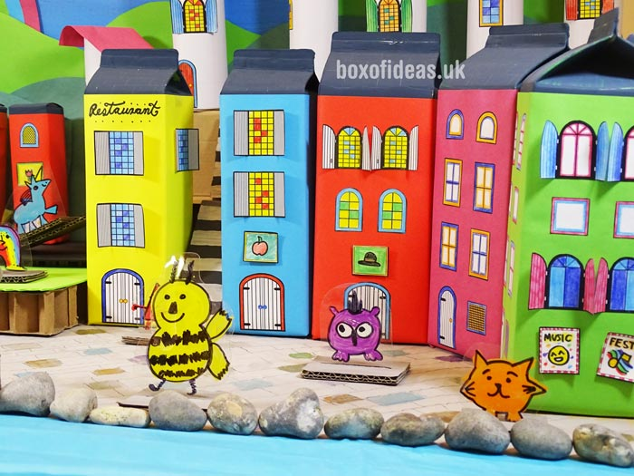 Colorful juice-box buildings for a recycled town project. A fun DIY kids craft toy made out of recycling. #recycledcrafts #kidscrafts