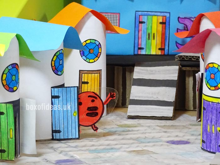 Colorful cardboard tube houses for a recycled town project. A fun DIY kids craft toy made out of recycling #kidscrafts #tubecrafts