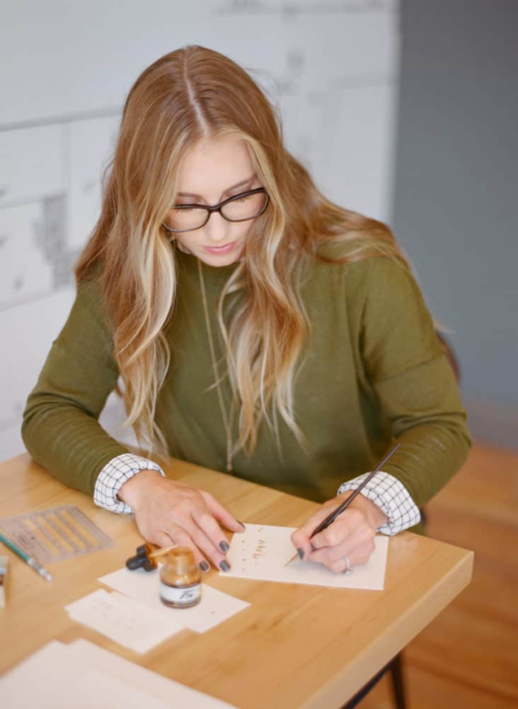 Girl writing calligraphy on paper