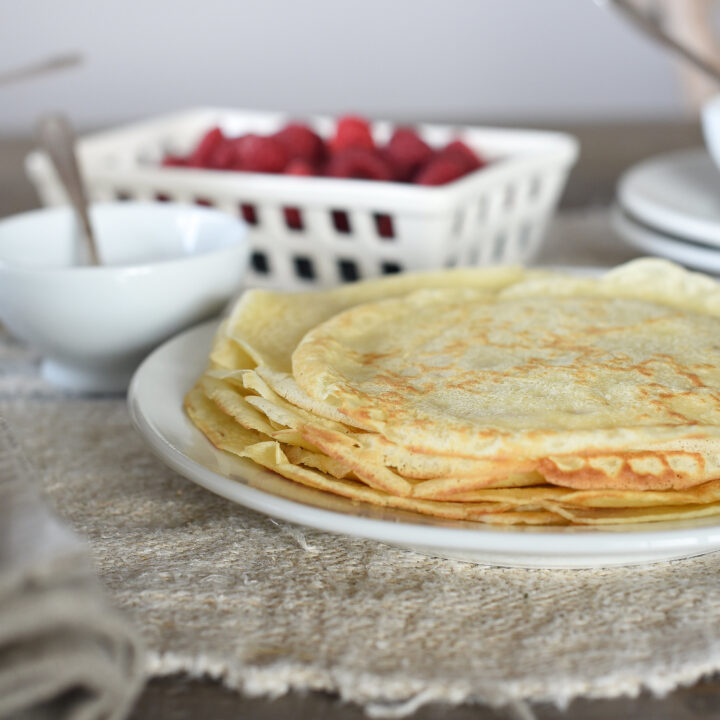 Delicious French Crepes layered on one another with raspberries