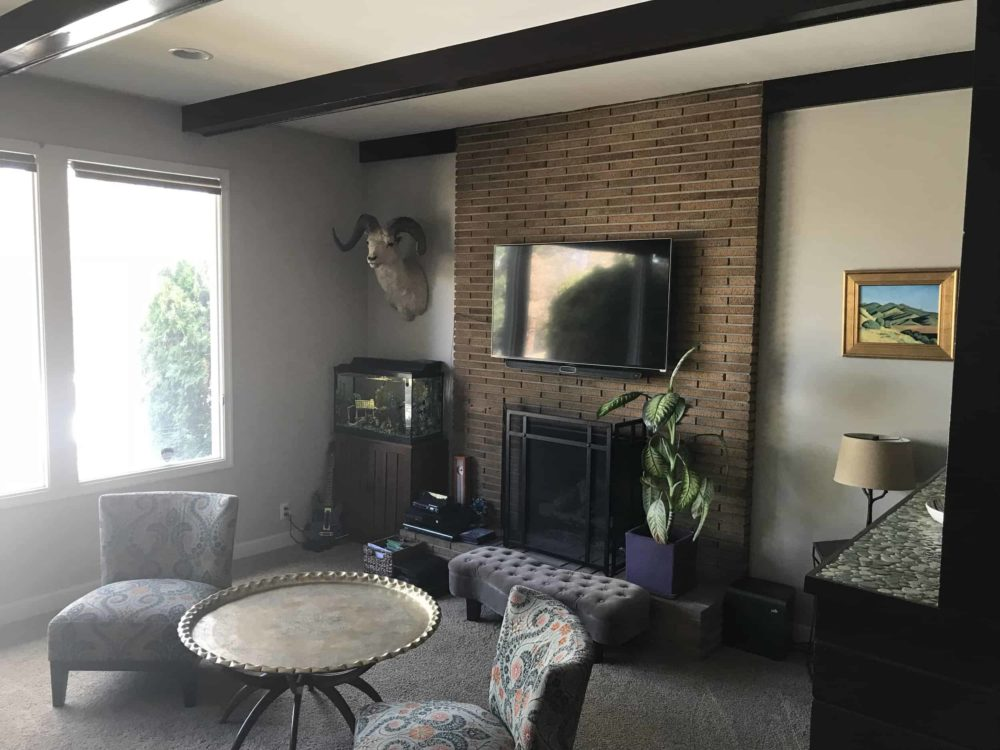 Brick Fireplace with TTV above fireplace and living room furniture