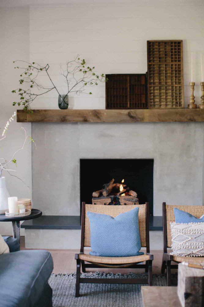 Cement fireplace with reclaimed wood beam, with living room furniture