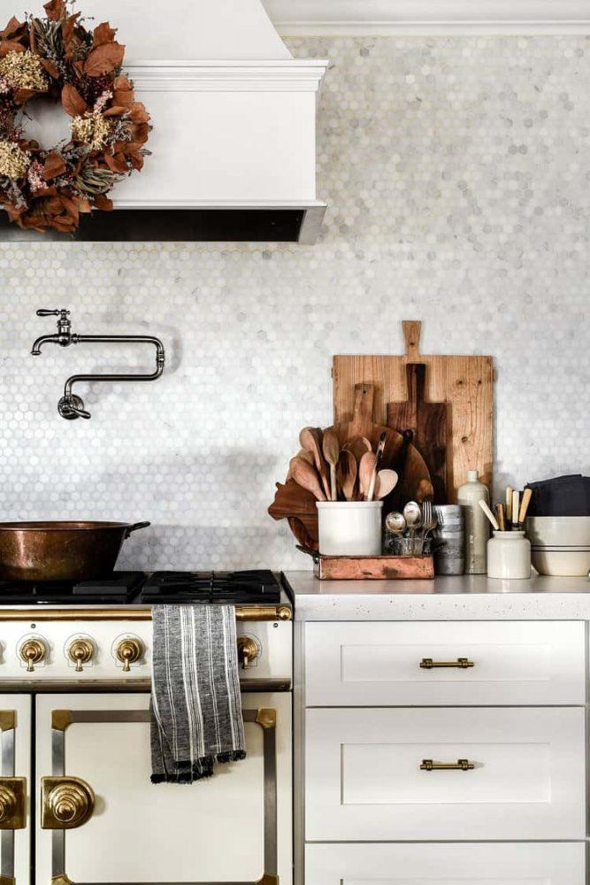 White modern farmhouse kitchen range and countertop with marble backsplash tile.