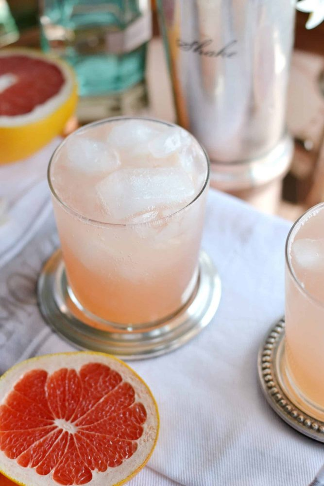 Grapefruit and Gin cocktail on a silver coaster with grapefruit slices