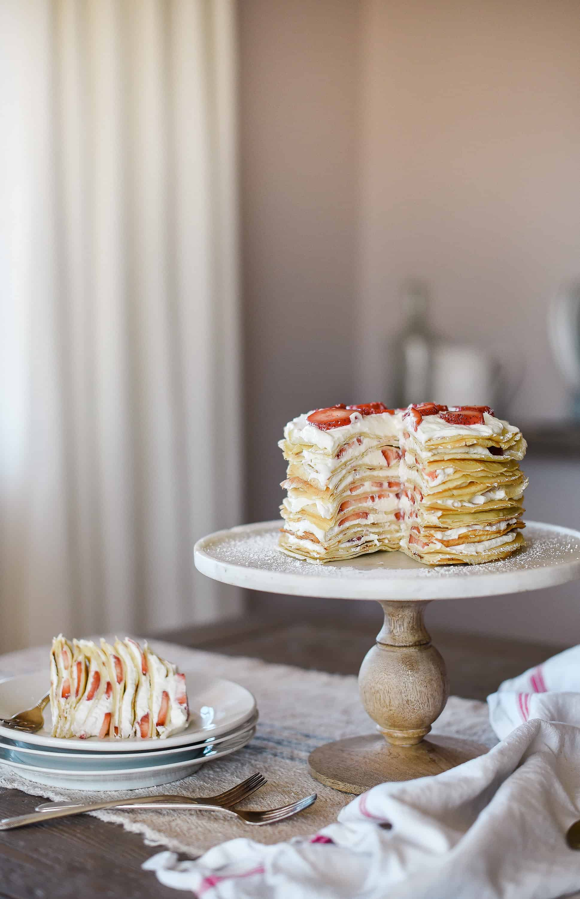 This crepe cake recipe is a show-stopper, and is perfect for special occasions! The cake is made of delicate crepes and filled with strawberries & whipped cream!