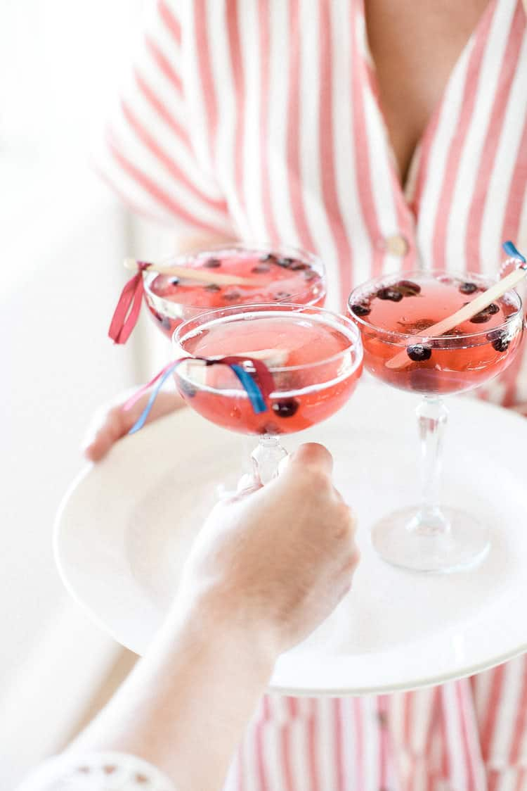 Get the recipe for this easy patriotic champagne cocktail the enjoy on 4th of July! And make sure to check out all of our favorite 4th of July party ideas while you're here!