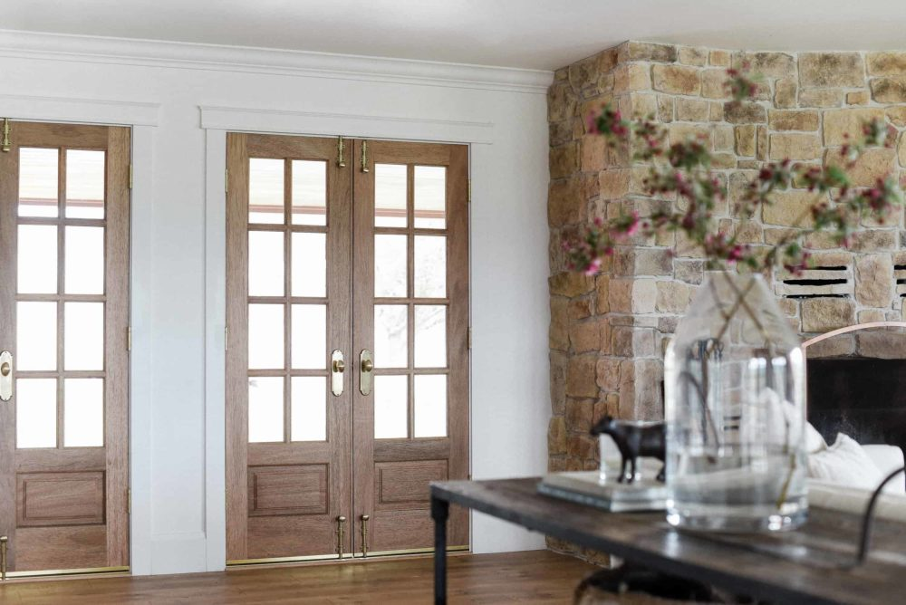 Wooden French Doors in living room next to stone fire place