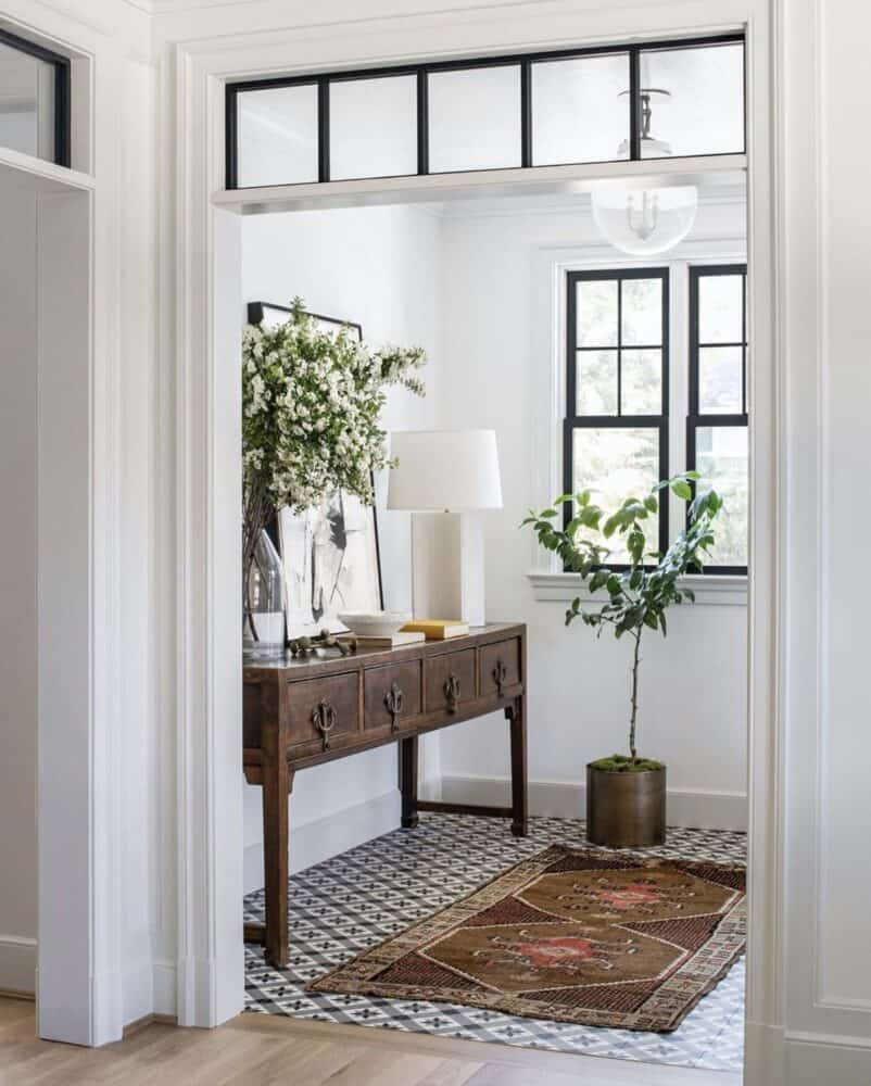 Entryway with Patterned tile and vintage rug by Anderson Wier Studio