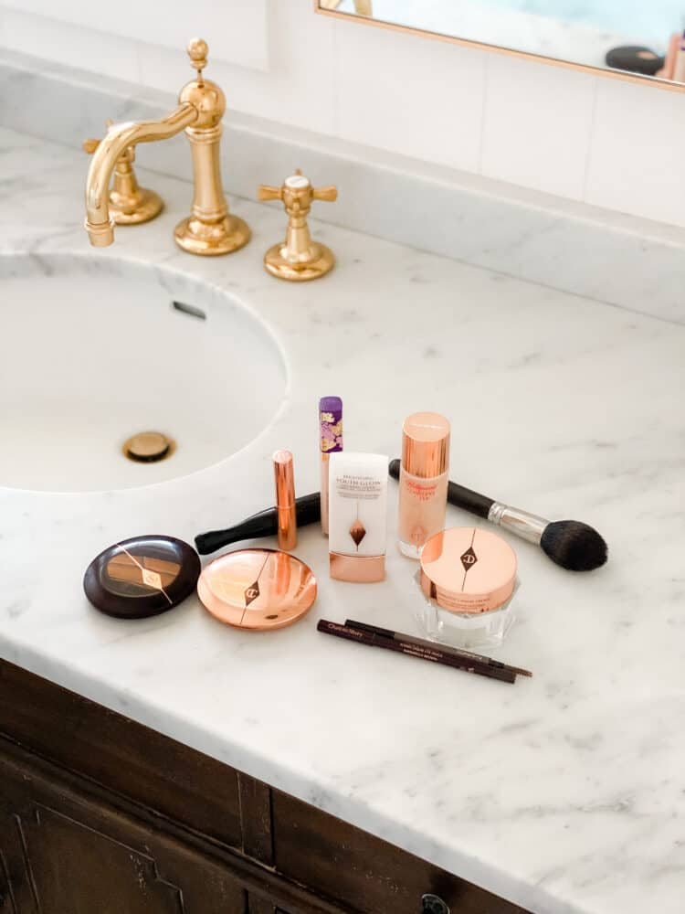 Makeup on marble countertop with brass faucet