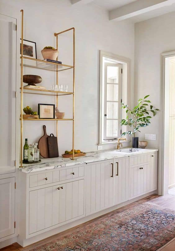 Beige cabinets with brass pipe open shelving