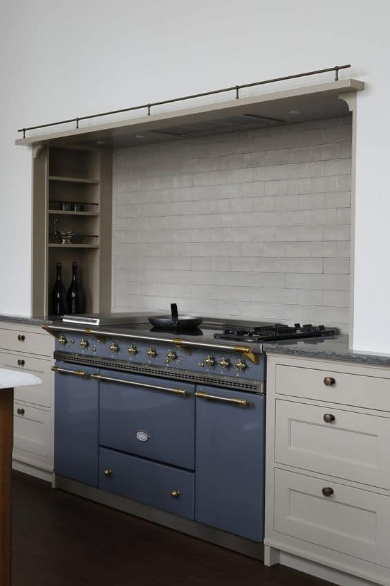 Taupe cabinets next to a navy blue range with beige tile