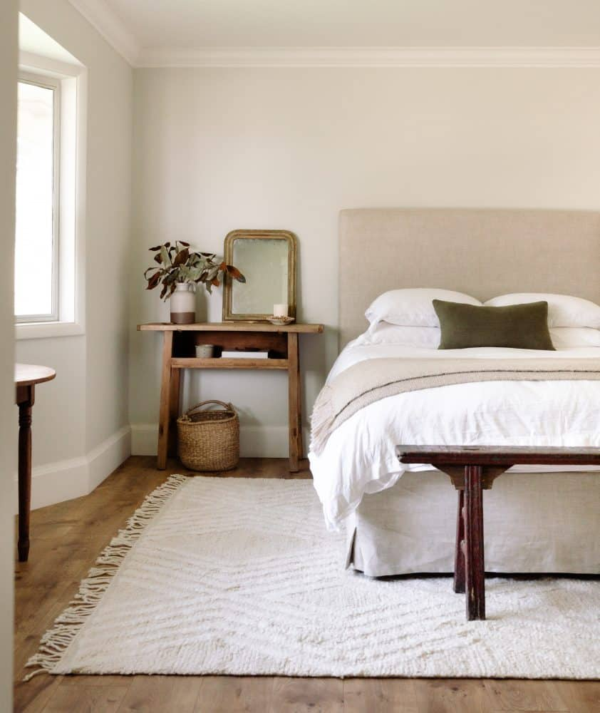 airy bedroom with grey walls and white rug with linen headboard and bench