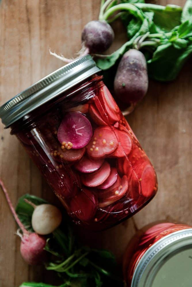 Jar of pickled radishes on table