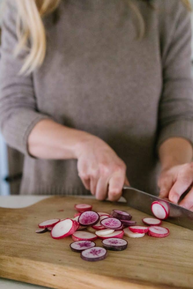 Girl cutting radishes in farmhouse kitchen